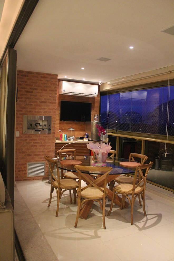 Varanda gourmet simples com mesa de vidro.
