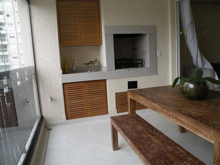 Varanda gourmet simples com armário de madeira e mesa rústica.