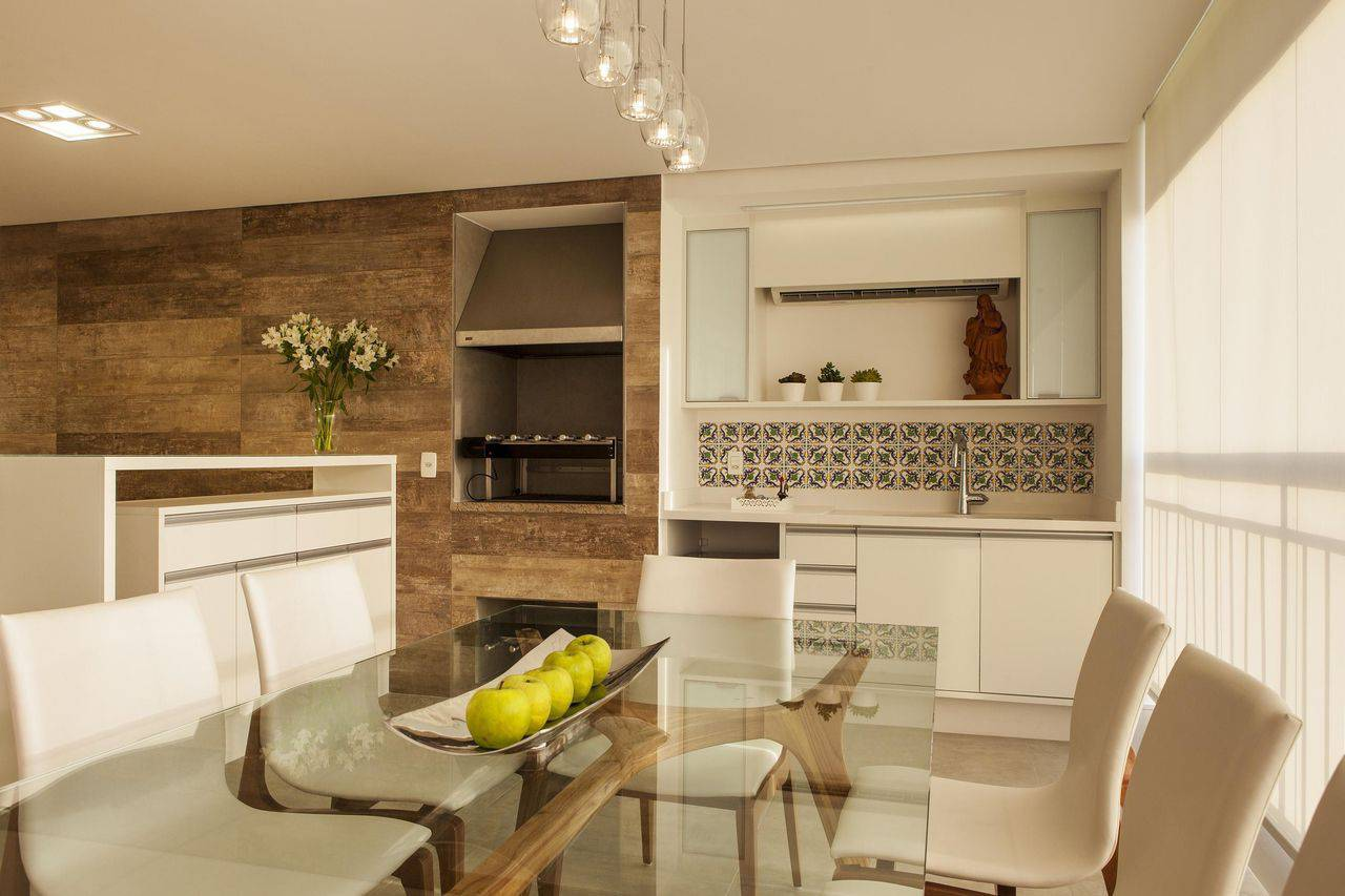 Varanda gourmet luxuosa com cozinha e pendente suspenso.