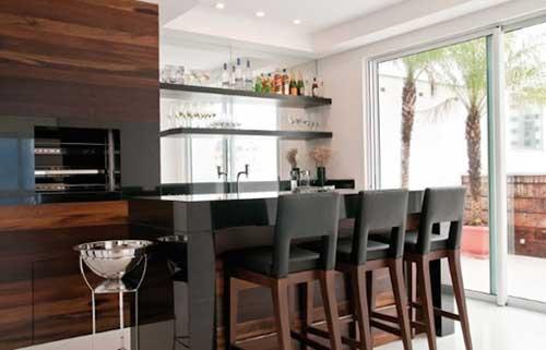 Varanda gourmet moderna com acabamento de madeira e bancada de porcelanato.