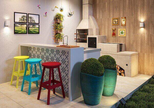 Varanda gourmet com decoração colorida e vaso de planta.