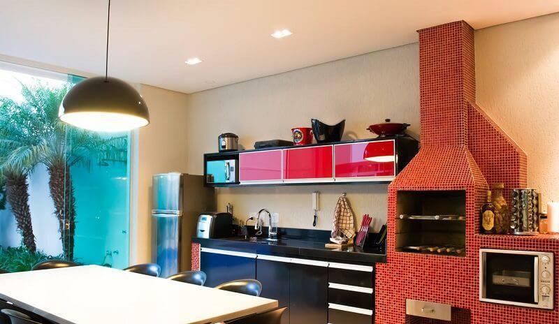 Área externa moderna com churrasqueira de alvenaria com pastilha vermelha.