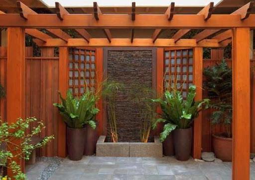 Pergolado de madeira com vasos de plantas.