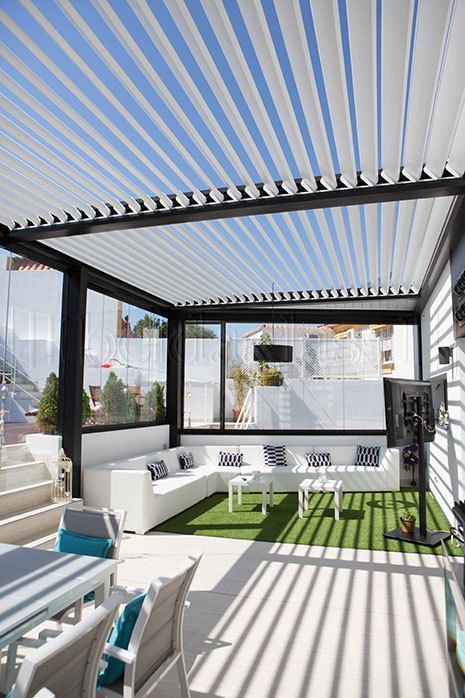 Área com sofá branco e grama sintétitca.