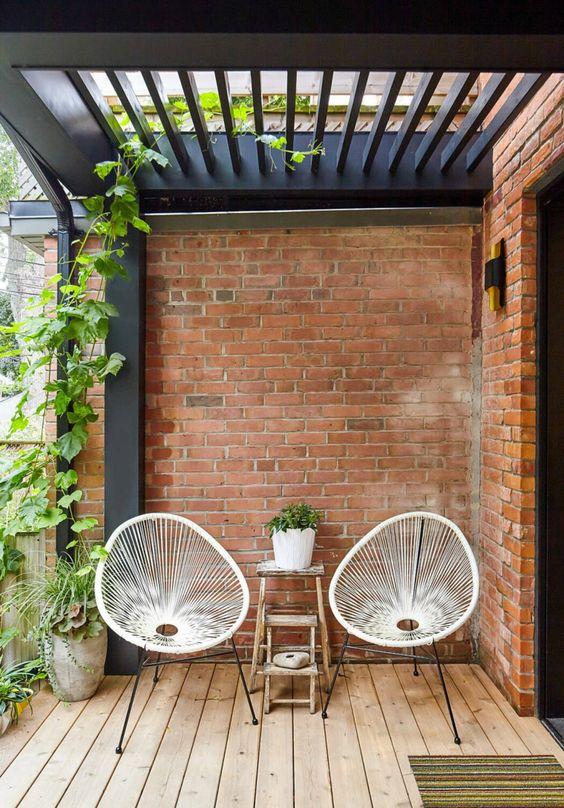 Varande de tijolos a vista com duas cadeiras.