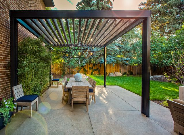 Área externa com mesa e cadeiras de madeira com estofados azuis.
