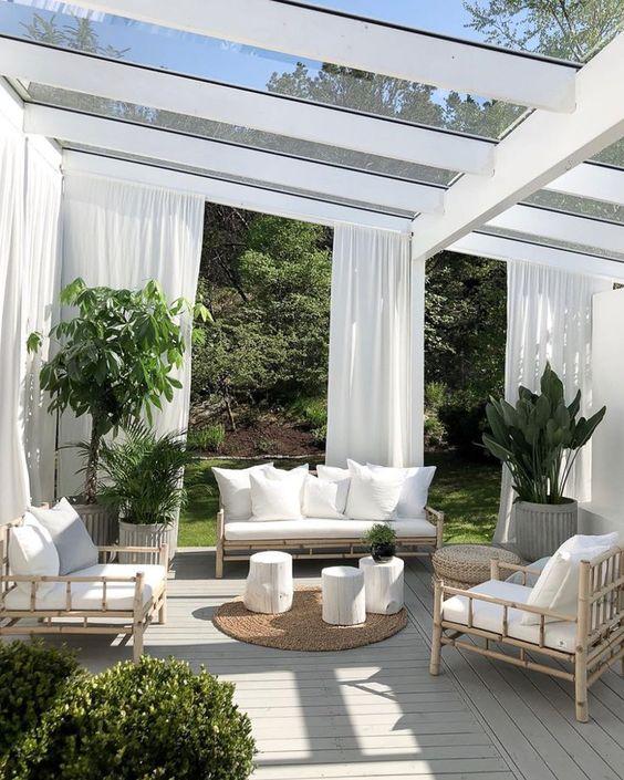 Deck de madeira com sofás brancos, plantas e tecidos.