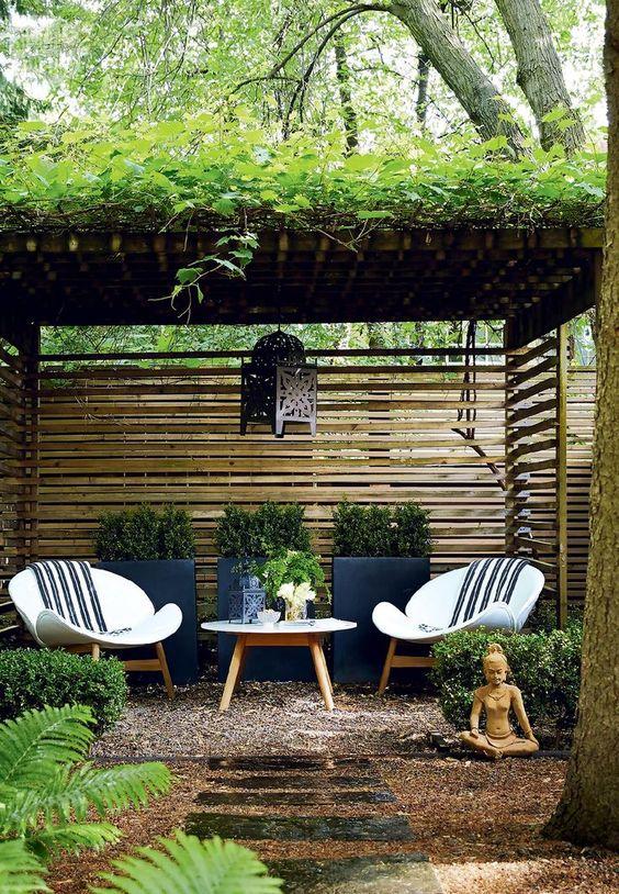 Área externa com vasos de plantas, poltronas e mesa de centro.