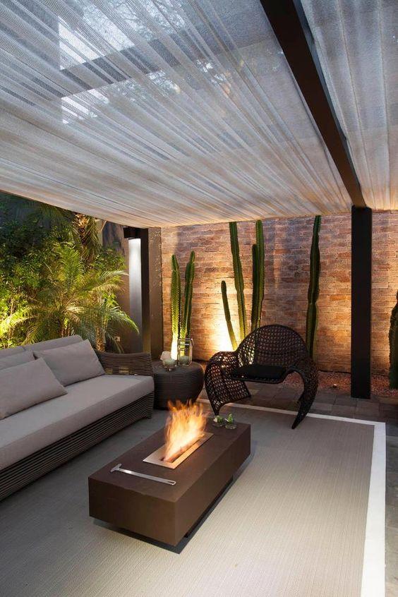 Sala decorada com lareira, plantas e pergolados com tecido.