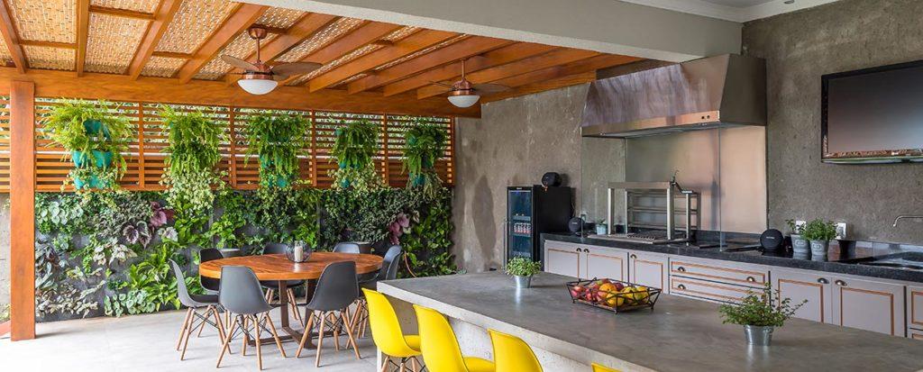 Cozinha gourmet com pergolado e plantas.
