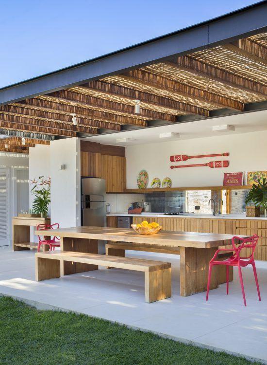 Cozinha gourmes com mesa de madeira e cadeiras rosa.