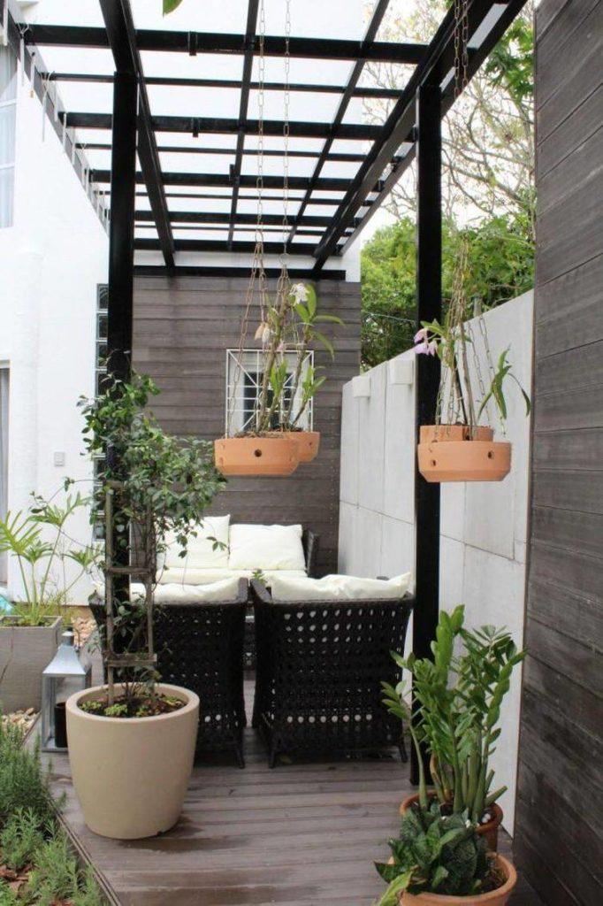 Pergolados pretos com vasos de plantas.