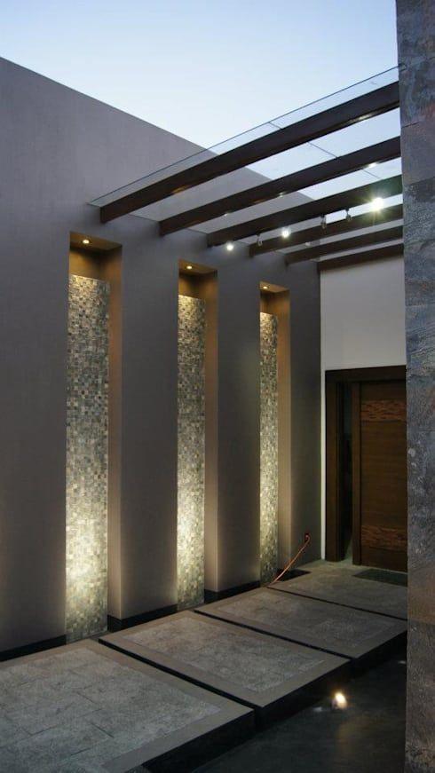 Entrada com muro iluminado e pergolados.