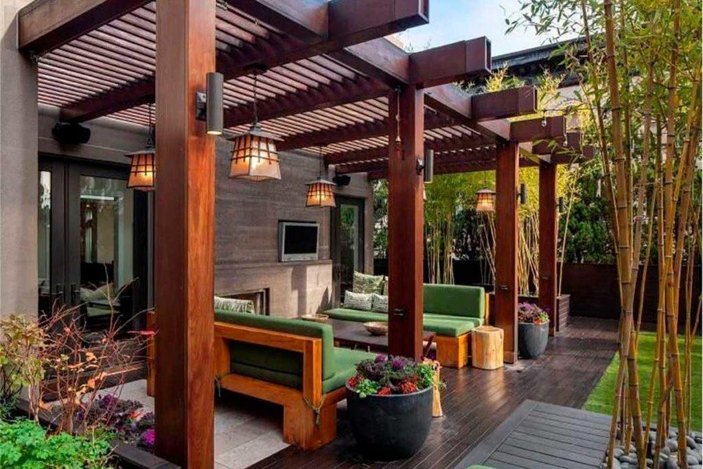 Varanda com sofás verdes e gramado.