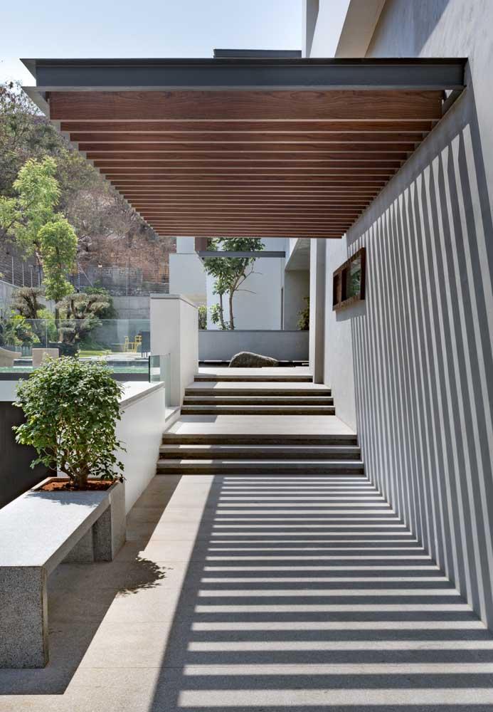 Casa moderna com pergolados na entrada.