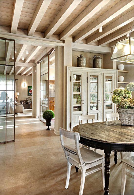 Casa com pergolados e teto de madeira.