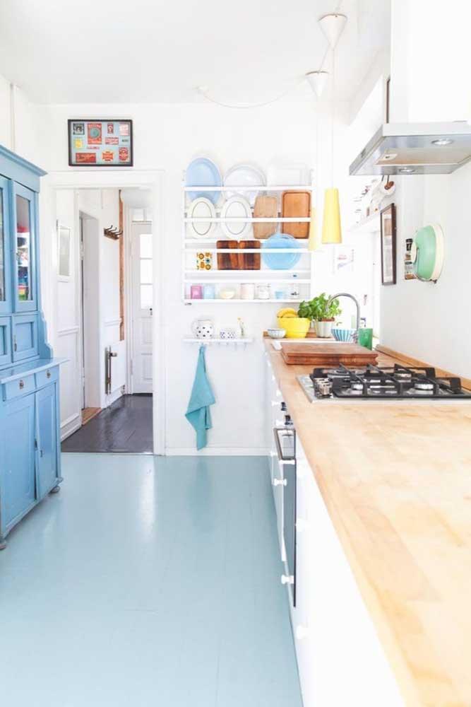 Cozinha pequena branca com piso vinílico azul.