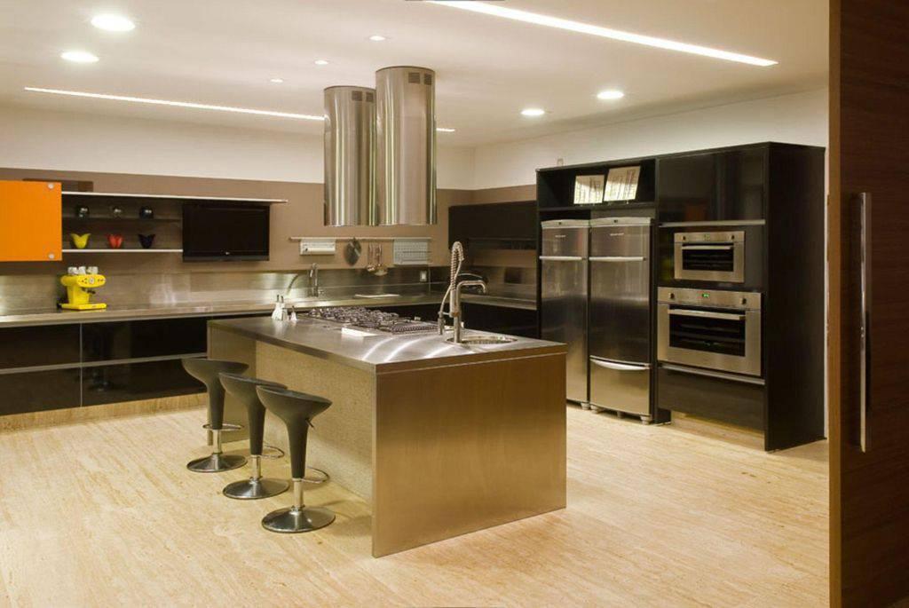 Cozinha com ilha de aço inox e coifa modena.