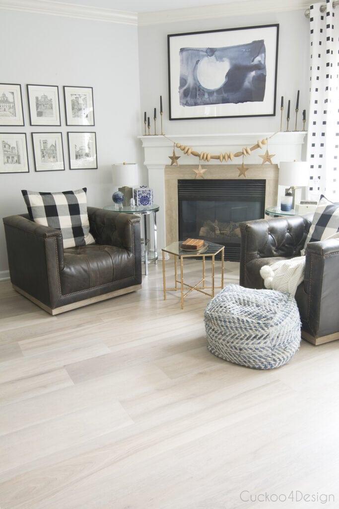 Sala de estar com lareira, poltronas de couro e piso vinílico.