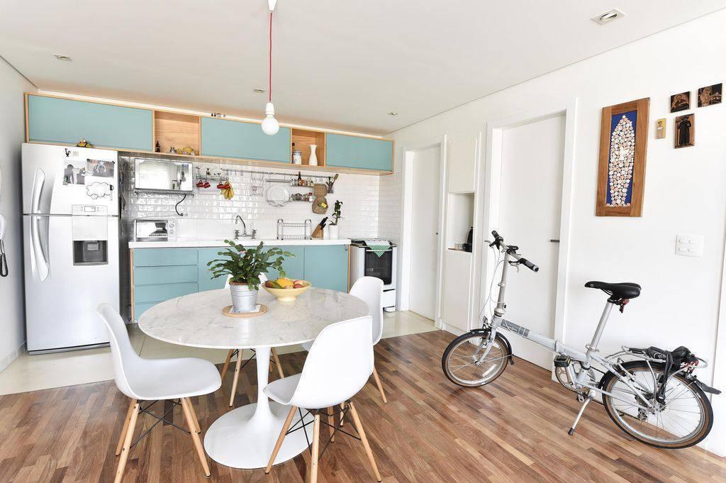 Cozinha pequena aberta azul com sala de jantar integrada.