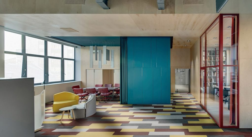 Sala de trabalho com piso vinílico colorido.