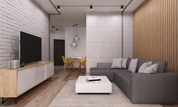 Sala de estar com sofá em L e parede de tijolinho aparente.