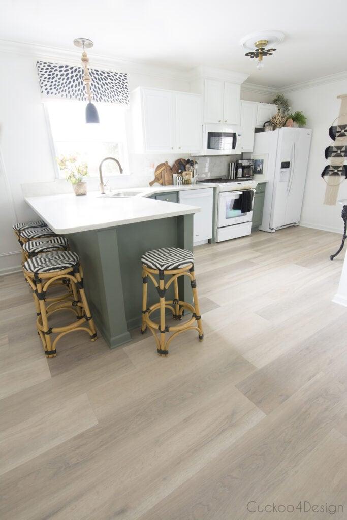 Cozinha em L simples com piso vinílico.