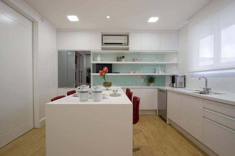 Cozinha com ilha simples e piso vinílico.