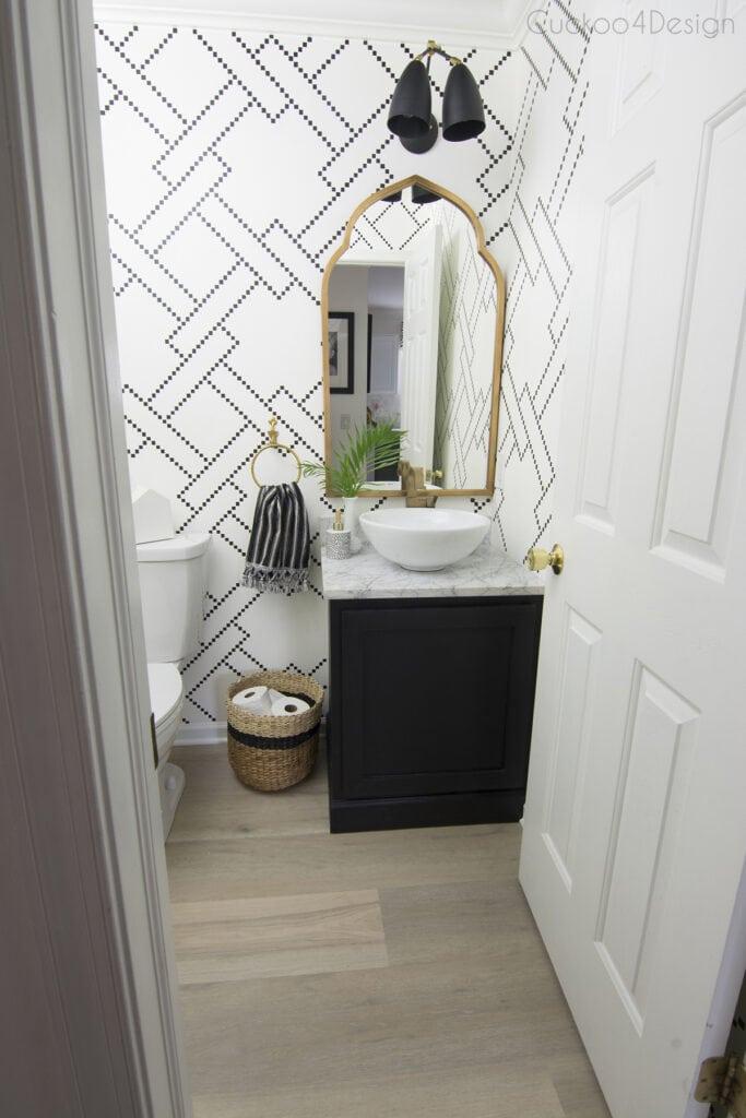 Banheiro moderno com papel de parede decorado e piso vinílico.