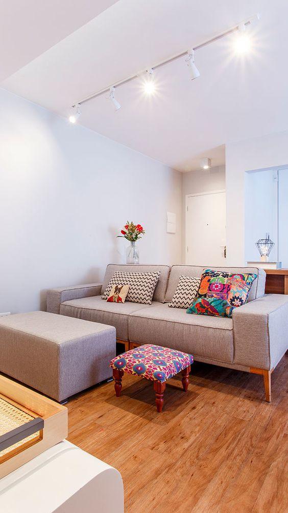 Sala simples com sofá cinza e almofada decorada.