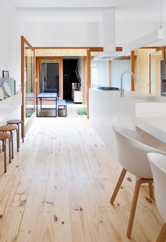 Cozinha aberta branca com piso vinílico.