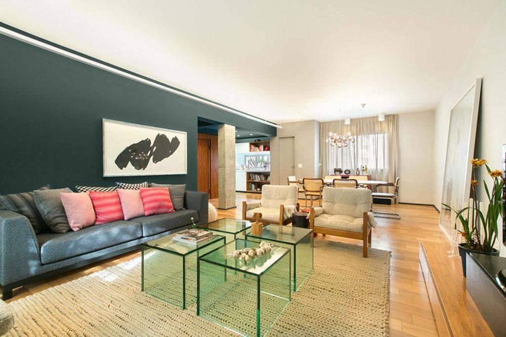 Sala de estar moderna com mesa de centro de vidro e piso vinílico.