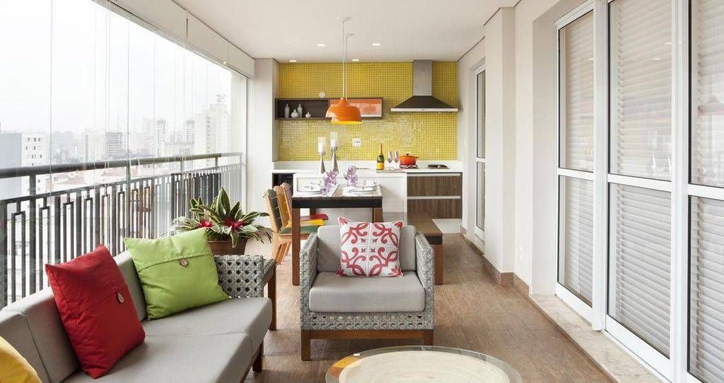 Varanda gourmet com sala e piso vinílico.
