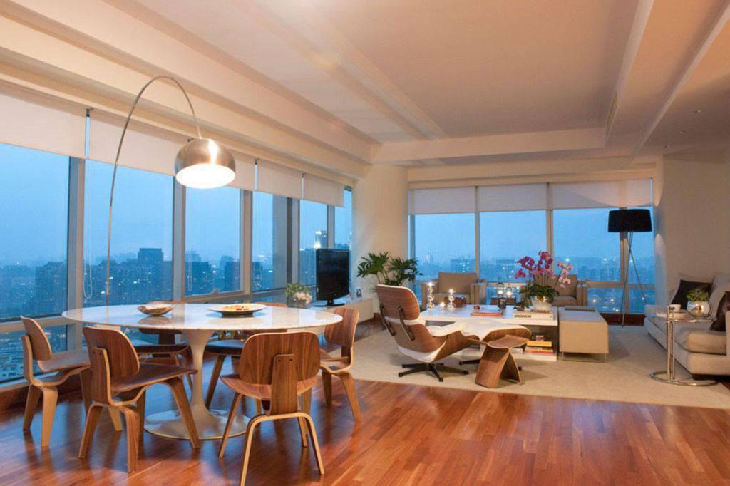 Sala com decoração neutra e móveis de madeira.