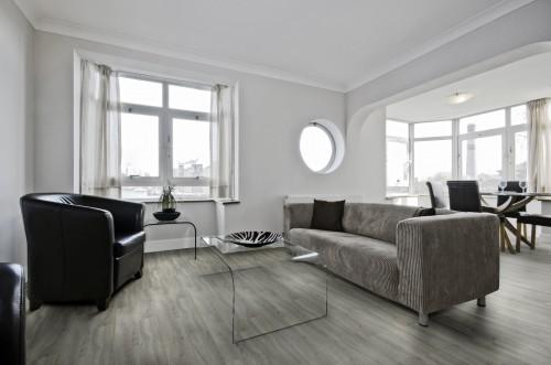 Sala moderna com sofá cinza e piso vinílico.