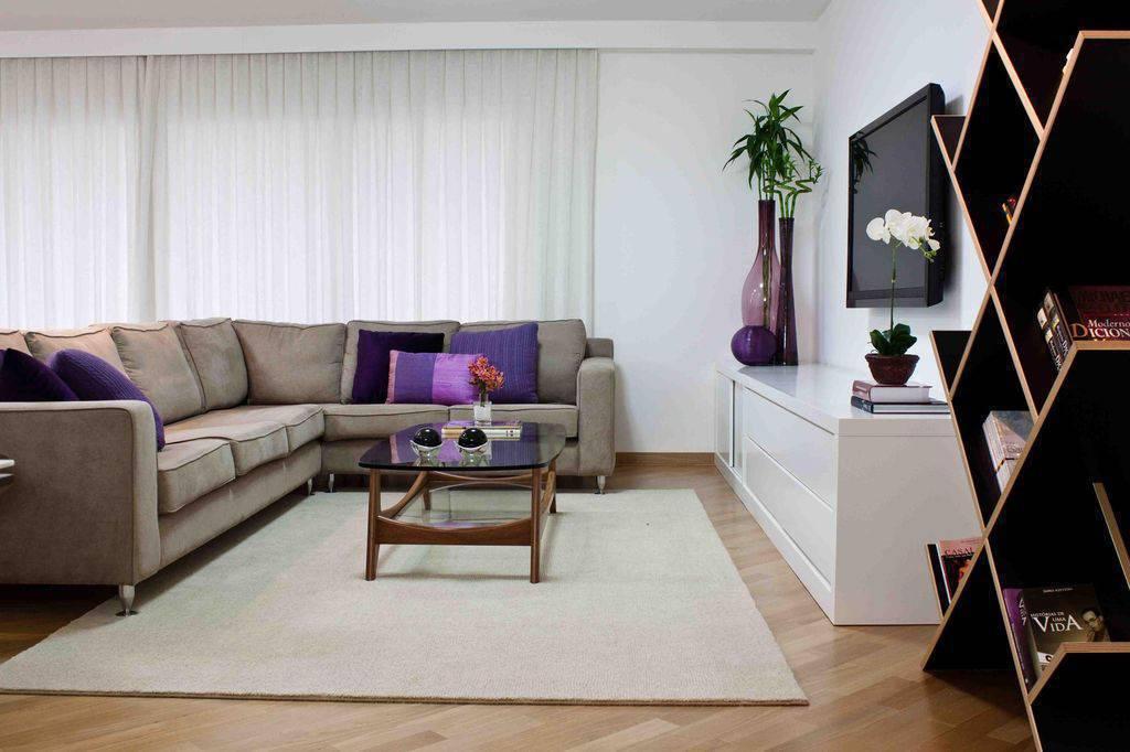 Sala de estar simples com decoração cinza e roxa.