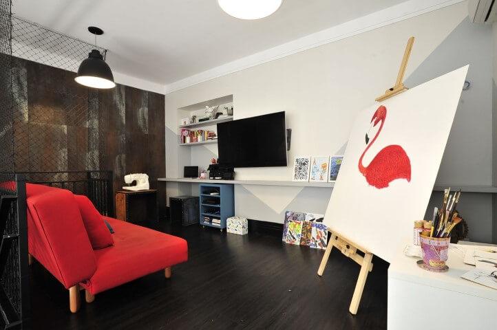 Sala moderna com sofá vermelho e espaço para pintura.