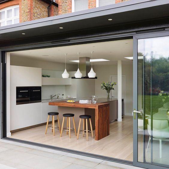 Cozinha gourmet com porta de vidro.