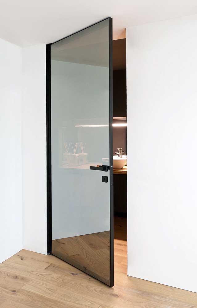 Parede branca com porta de vidro de moldura preta.