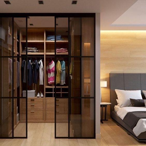 Closet masculino com camisas penduradas em cabides.