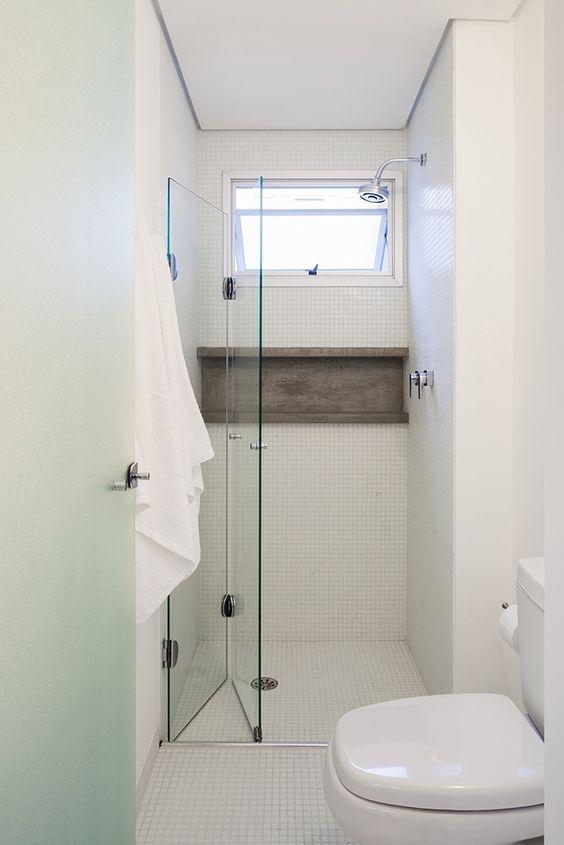 Banheiro branco com nicho amadeirado.