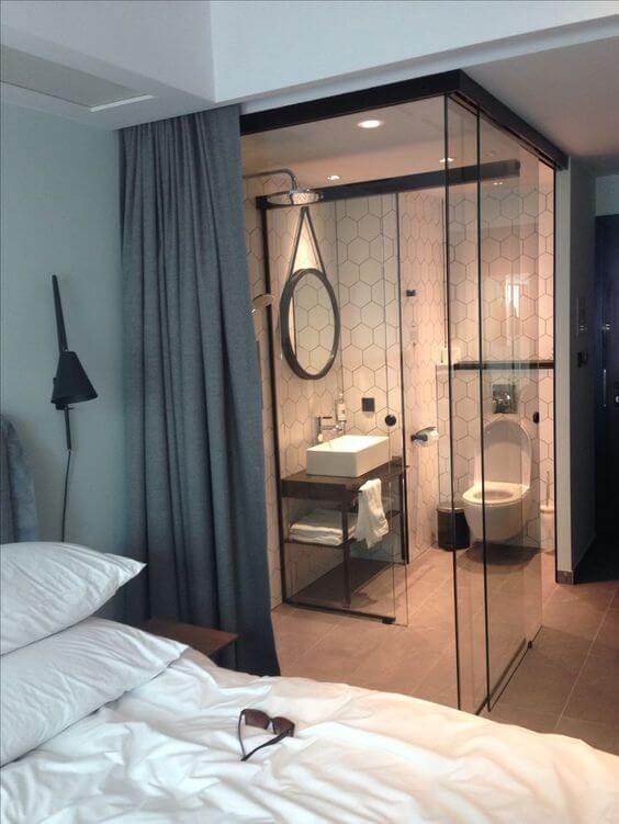 Banheiro com paredes e porta de vidro.
