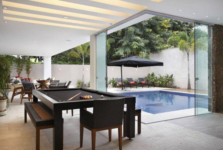 Área de lazer com piscina e mesa de bilhar.