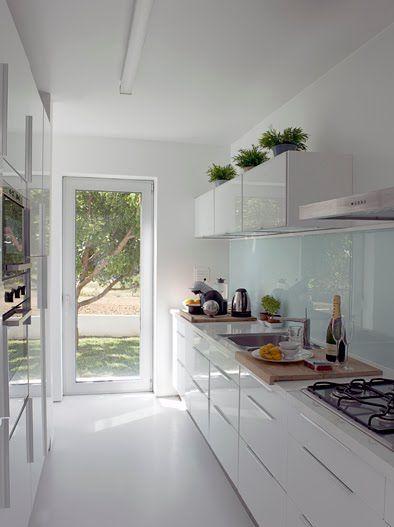 Cozinha toda branca com vasos de plantas.