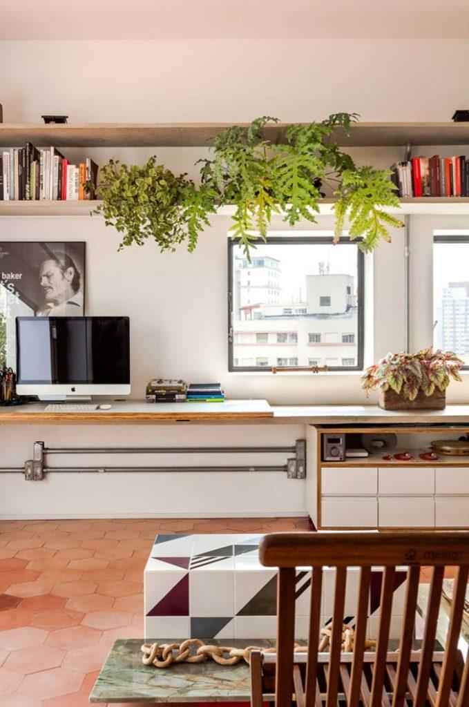 Estante decorada com livros e plantas.