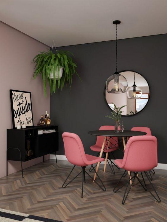 Sala de jantar moderna com mesa redonda, cadeiras rosas e espelho redondo.