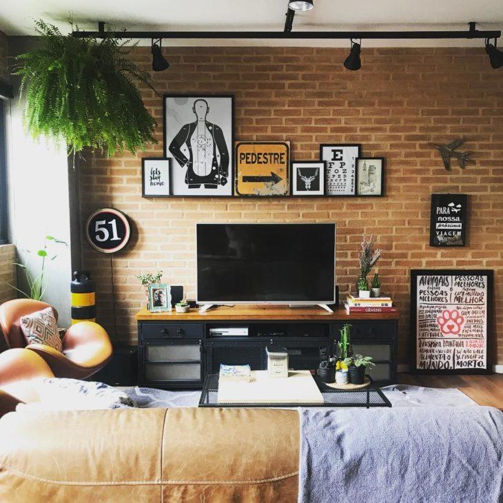Sala moderna com parede de tijolinho aparente e quadros.