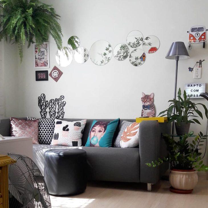 Sala pequena simples com plantas e espelhos.