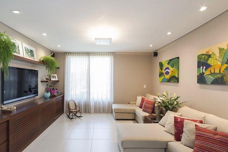 Sala decorada com samambaias e quadros.