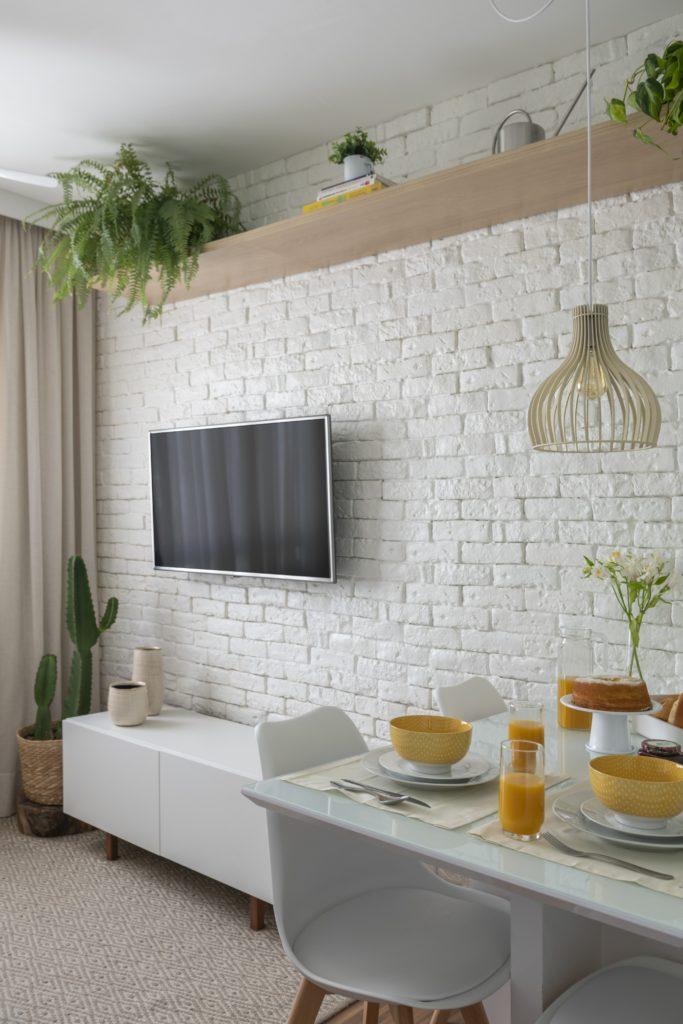 Sala pequena com decoração neutra e plantas.
